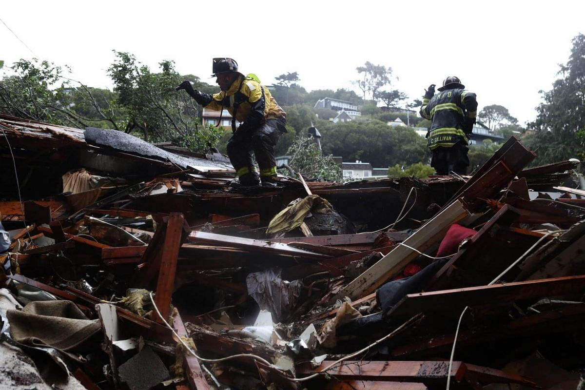 Southern Marin firefighters search a home that was swept down a hill by a mudslide during a storm in Sausalito, on Feb 14, 2019.
