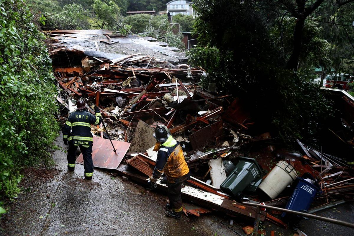 Southern Marin firefighters search a home that was swept down a hill by a mudslide during a rain storm in Sausalito, on Feb 14, 2019.