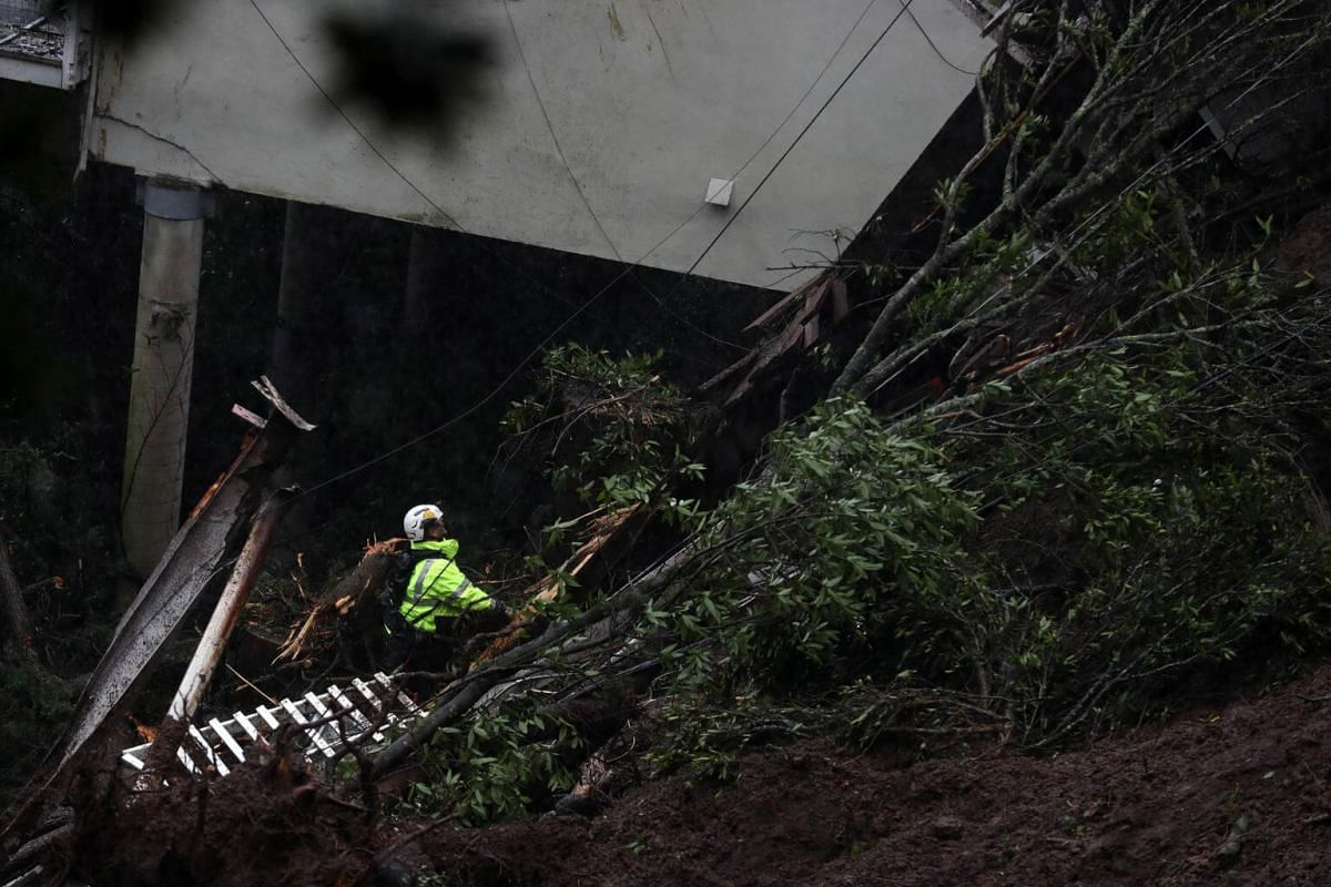 A search and rescue worker searches through debris next to a home that was swept down a hill by a mudslide in Sausalito.