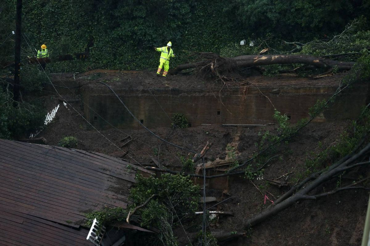 A worker walks through mud as he tries to get a better view of a home that was swept down a hill by a mudslide in Sausalito.