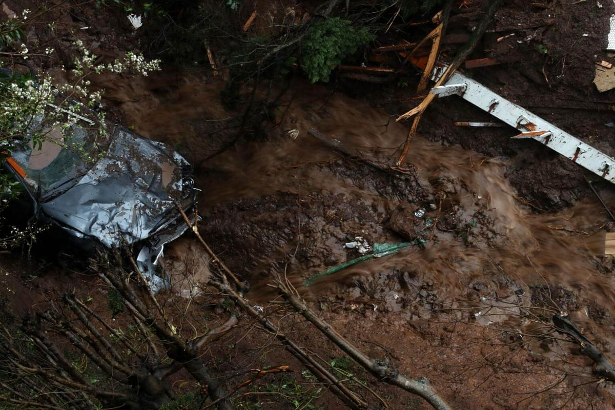 Water flows by a car that was swept down a hill by a mudslide in Sausalito.