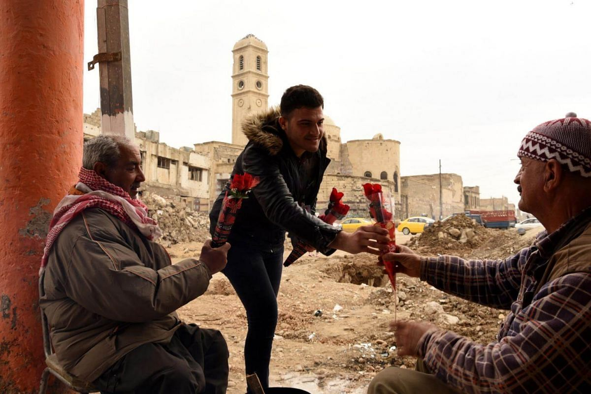 An Iraqi activist distributes red flowers on Valentine's Day near the ruins of destroyed buildings in Mosul.