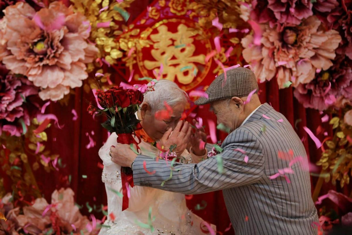 An elderly couple attend a wedding ceremony recreated for them by local charities on their 70th wedding anniversary on Valentine's Day in Jiaxing, Zhejiang province, China.