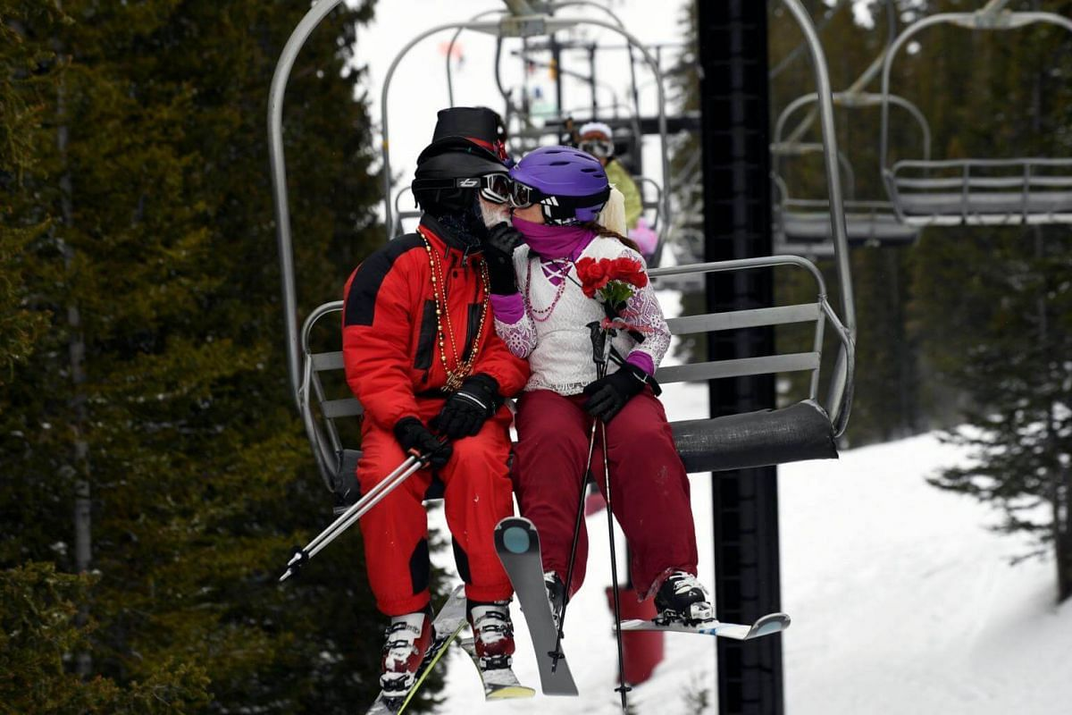 Clark and Barbara Shivley kiss while riding a chair lift during the 28th Annual Valentine's Day Mountaintop Matrimony ceremony at Loveland Ski Area near Georgetown, Colorado.