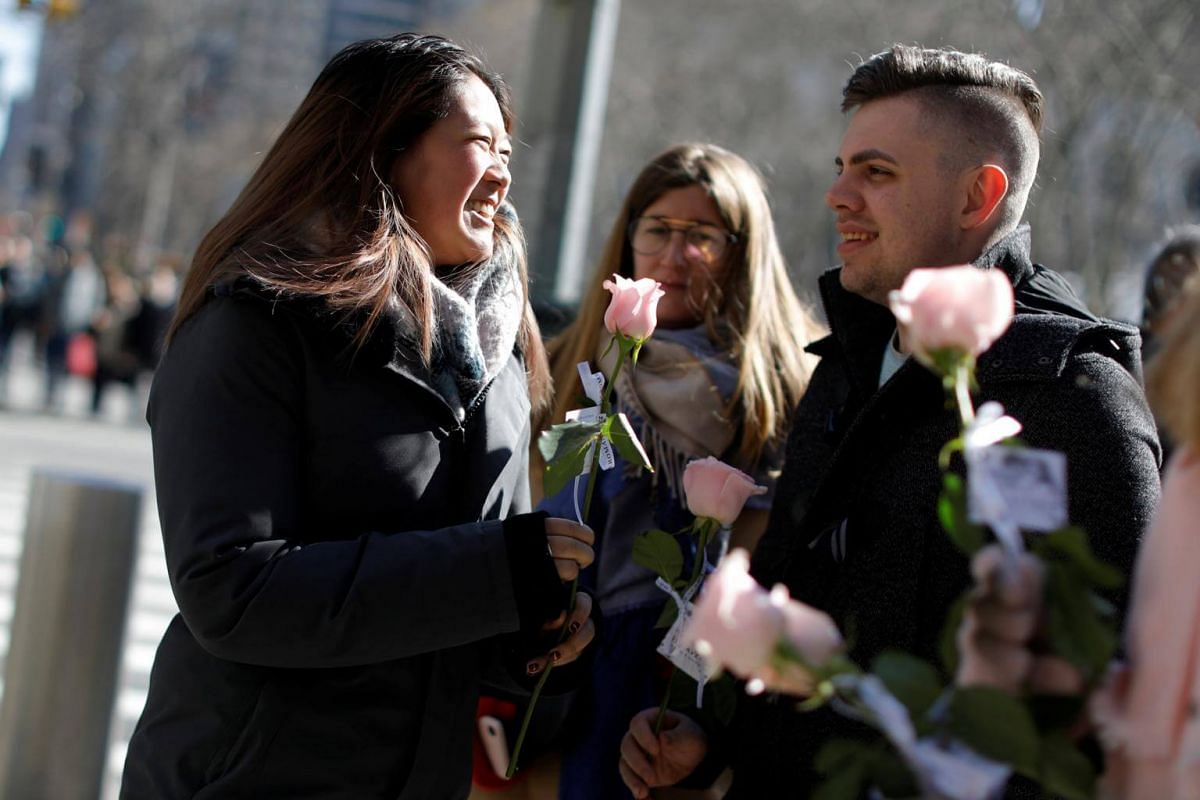 A couple receives pink roses on Valentine's Day on 6th Avenue in Manhattan in New York City.