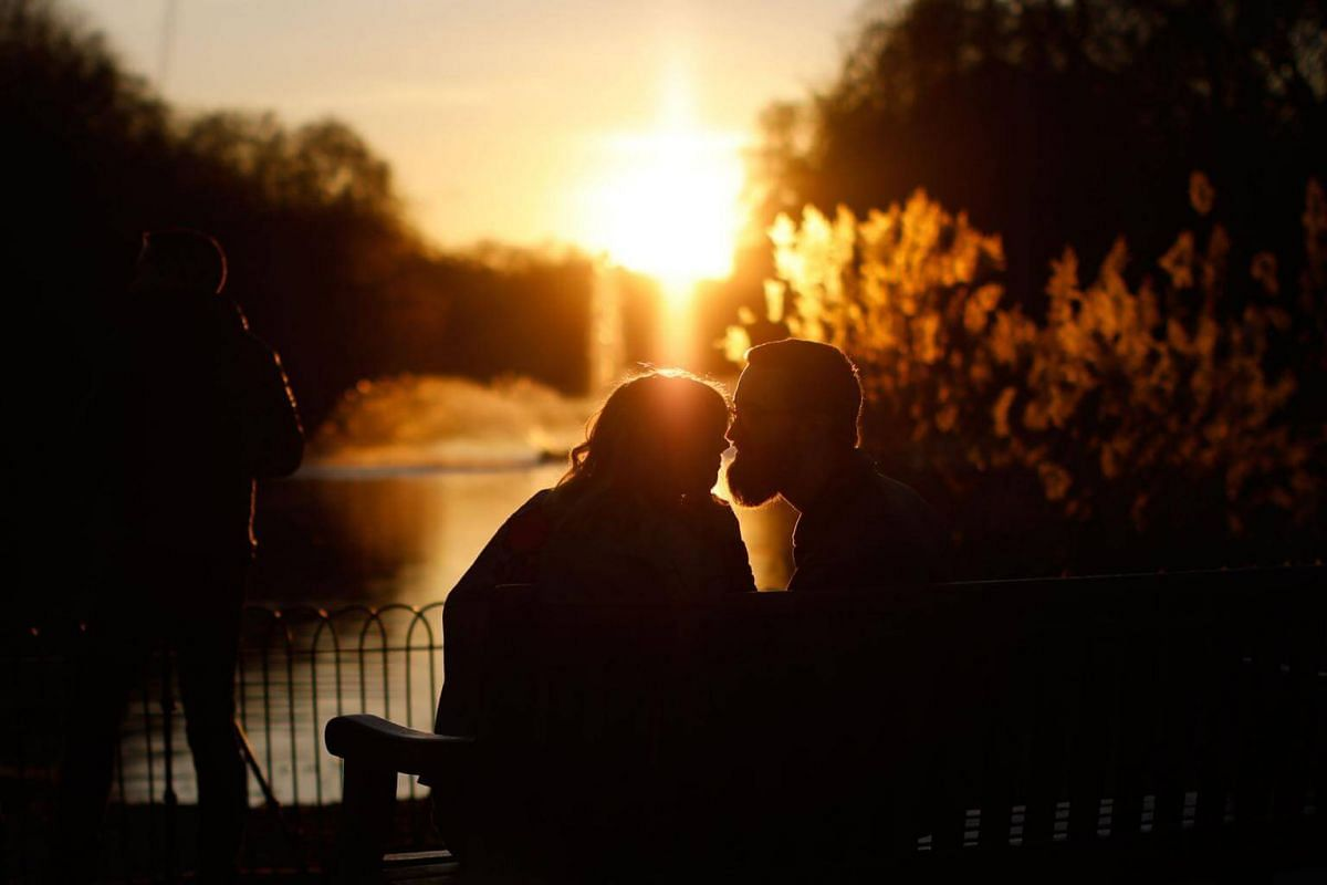 A couple kiss as the sun sets in St James' Park, London, on Valentine's Day.