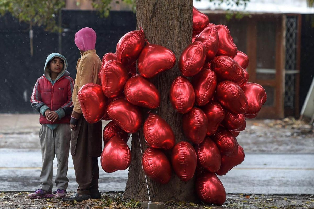 Young Pakistani vendors stand next to heart-shape balloons as they wait for customers for Valentine's Day in Islamabad.