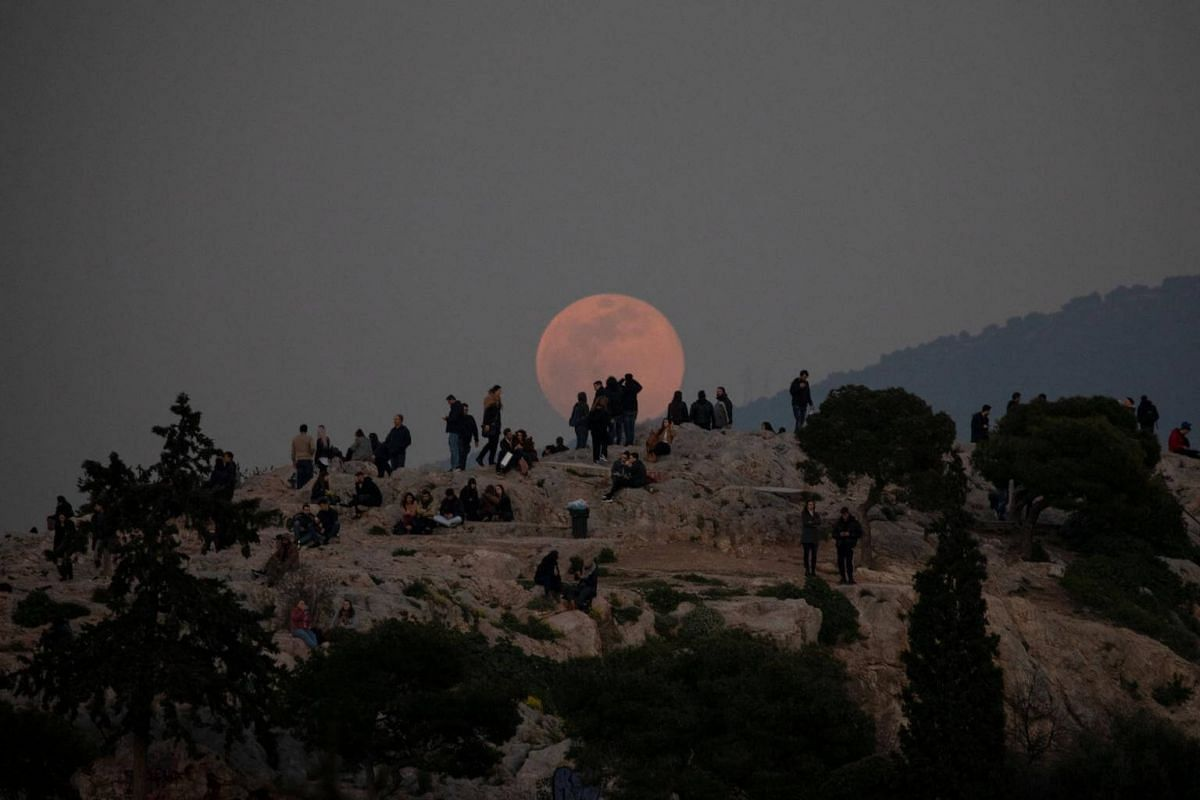 A super snow moon rises as people visit the Areios Pagos hill at the archaeological site of the Acropolis in Athens, on Feb 19, 2019.