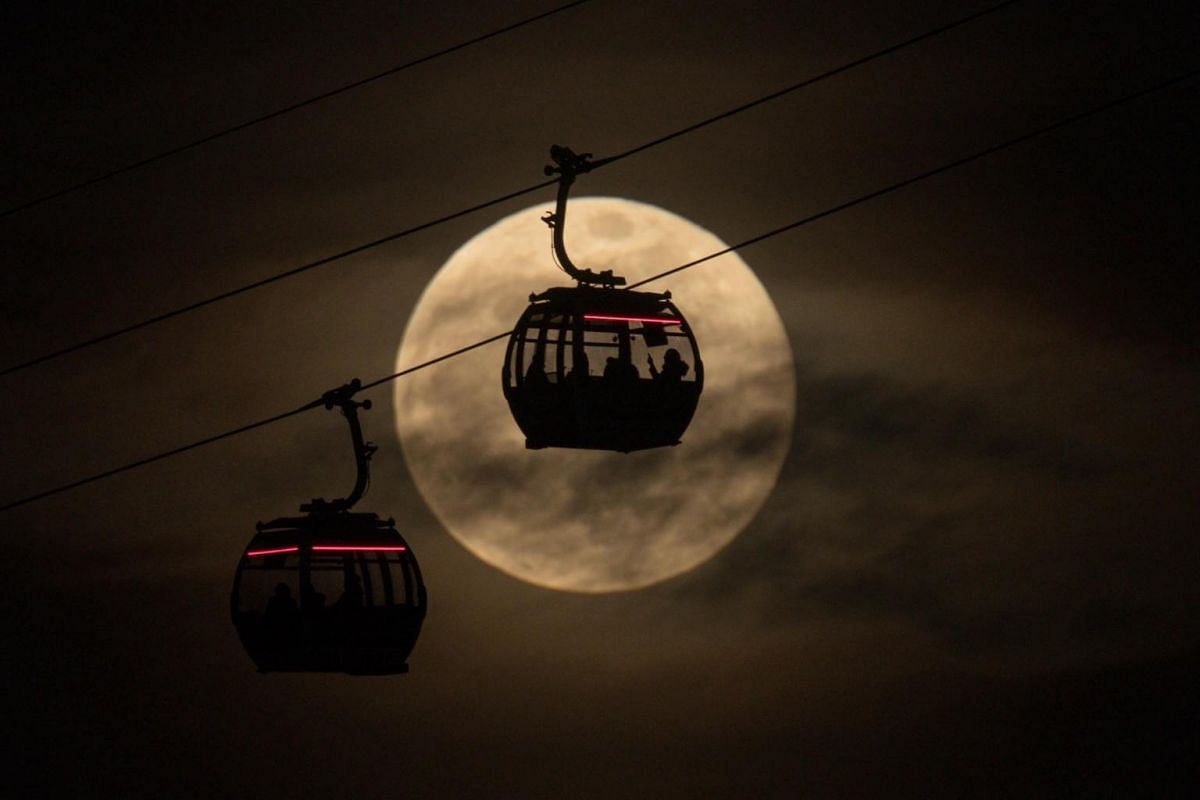 Emirates Air Line cable cars are silhouetted against the super snow moon at Greenwich in London, on Feb 19, 2019.