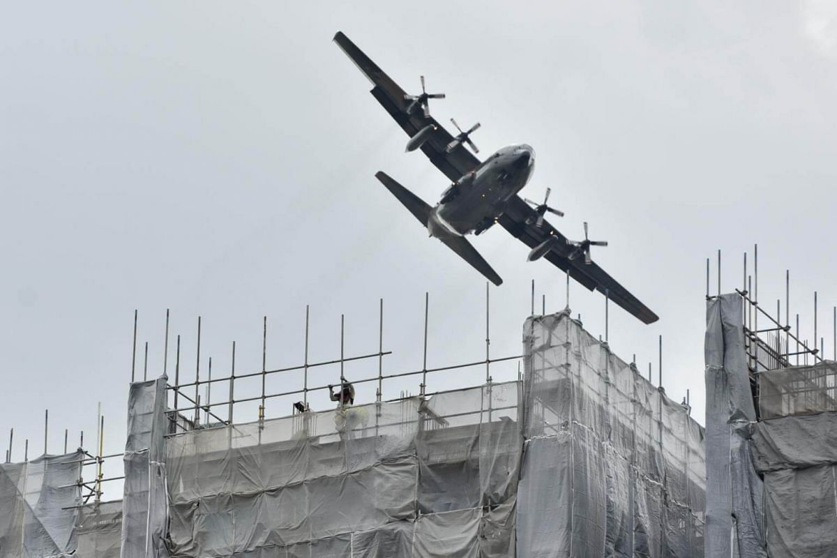 Construction workers working on a high-rise construction building while a Lockheed C-130 Hercules Republic Singapore Air Force airplane flies over them along Sims Avenue, on Jan 22, 2019.