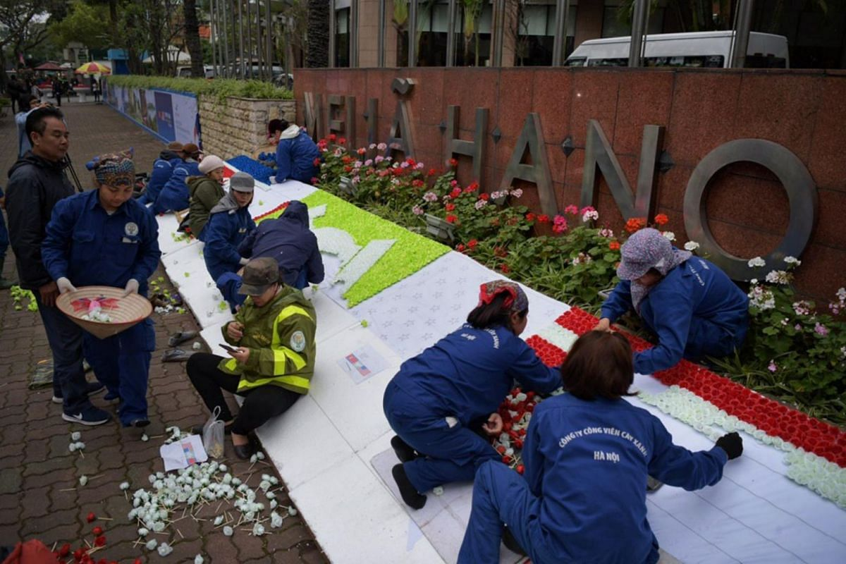 Workers putting up decorations made of artificial flowers outside the Melia Hanoi Hotel on Feb 25, 2019.