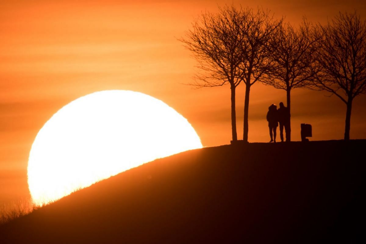 The silhouette of a couple stands out in front of the evening sky reddish by the sunset in Hannover, northern Germany on February 25, 2019. PHOTO: DPA VIA AFP