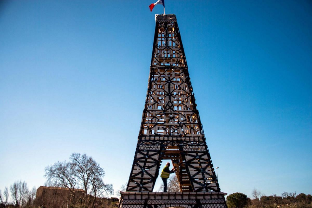 A protester climbs into an Eiffel Tour replica made by the Yellow Vests of 135 wood pallets in Le Luc, southeastern France on February 25, 2019. PHOTO: AFP