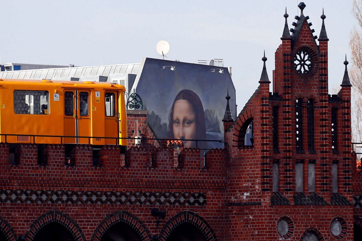 "A U-Bahn underground train passes by a mural by Berlin-based street art gang ""Die Dixons"" (The Dixons) which features a giant reproduction of Leonardo da Vinci's artwork Mona Lisa, near East Side Gallery, Germany, February 25, 2019. PHOTO: REUTERS"
