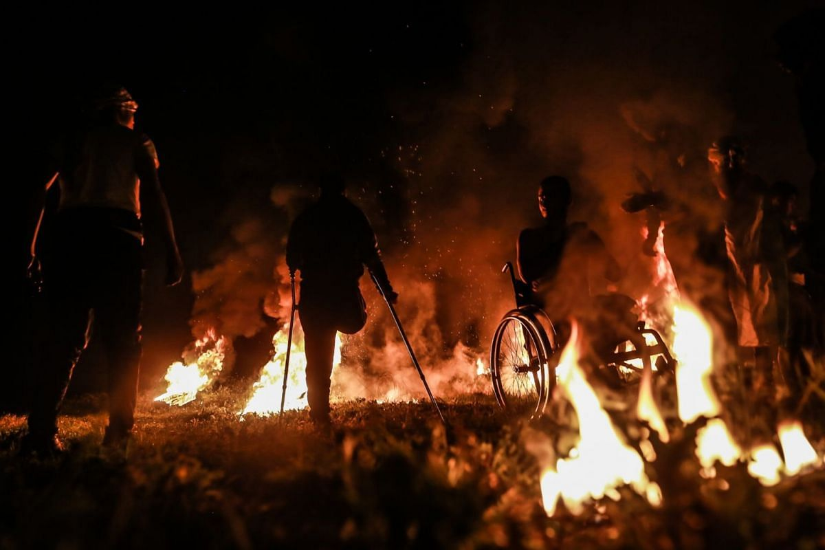 Palestinian protesters stand amid burning tires during a night demonstration and clashes with Israeli troops on February16,  2019, in the Palestinian Territories, Gaza. PHOTO: QUDS NET NEWS VIA ZUMA