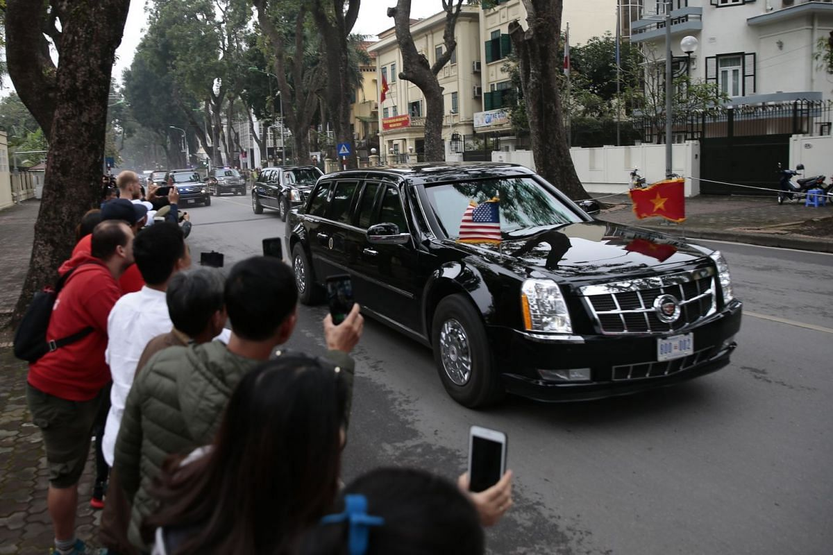 People take photos as a car transporting US President Donald Trump arrives for a state visit outside the Presidential Palace in Hanoi, Vietnam, on Feb 27, 2019.