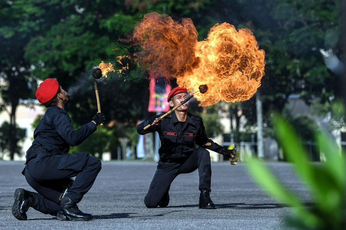 Members of Royal Malaysian Police perform with fire during the 63rd Federal Reserve's Anniversary Celebration and the National Heroes Service Medal Award at Federal Reserve Team Headquarters on February 26, 2019, Malaysia, Kuala Lumpur: PHOTO: BERNAM