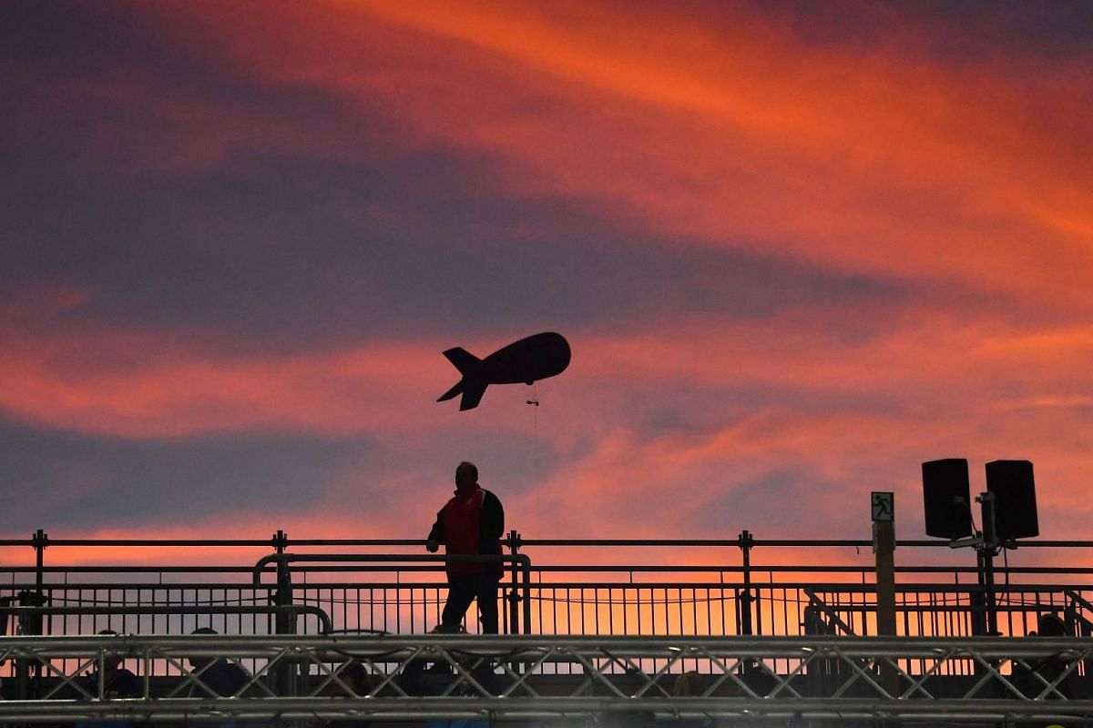 A zeppelin floats high in the sunset over a man at the Ladies team ski jumping event at the FIS Nordic World Ski Championships on February 26, 2019 in Seefeld, Austria. PHOTO: AFP