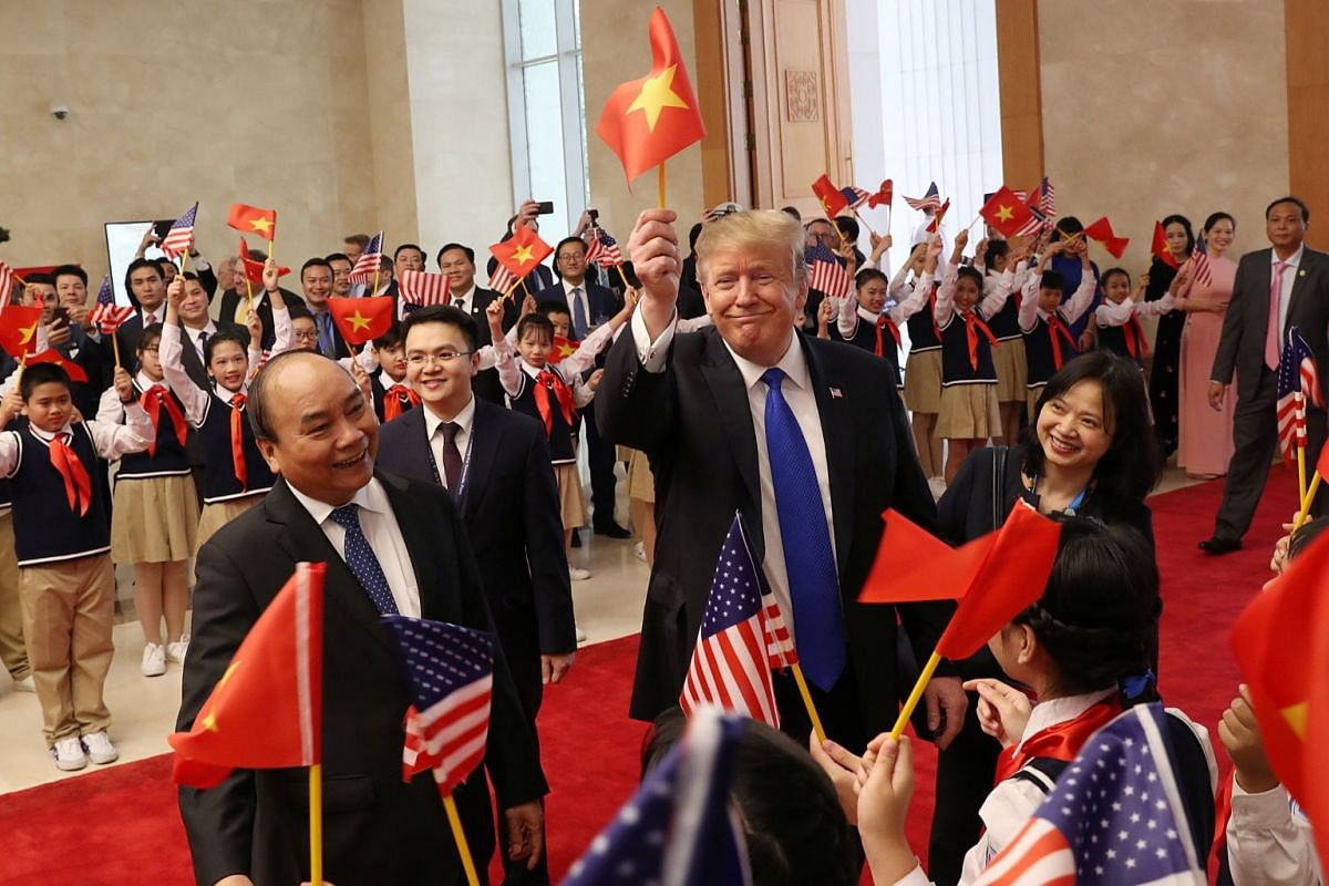 Vietnamese Prime Minister Nguyen Xuan Phuc (left) escorts US President Donald Trump as he is greeted by students at the Office of Government Hall in Hanoi, Vietnam, on Feb 27, 2019.