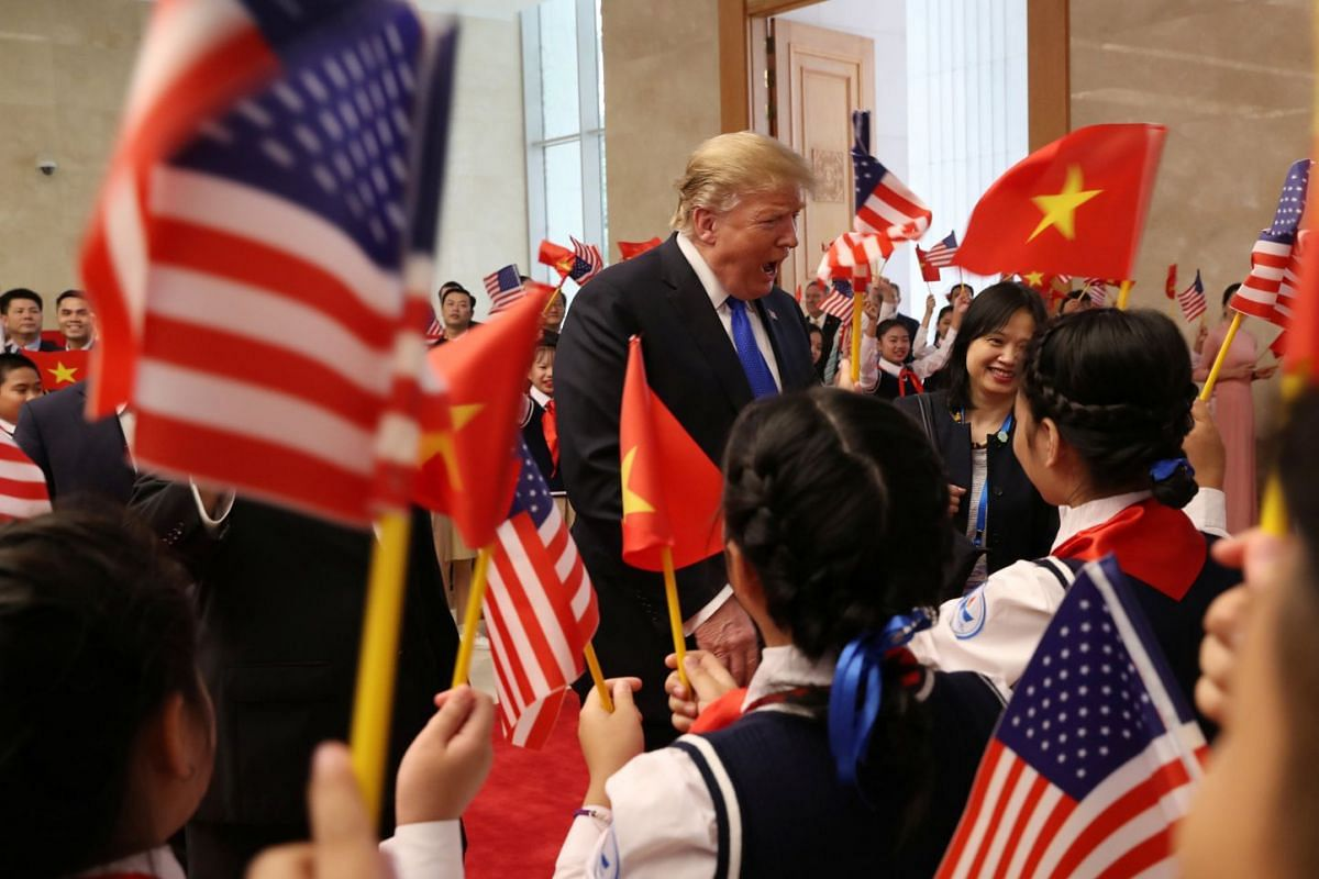 US President Donald Trump speaks to students waving Vietnam and US flags as they greet him at the Office of Government Hall in Hanoi, Vietnam, on Feb 27, 2019.