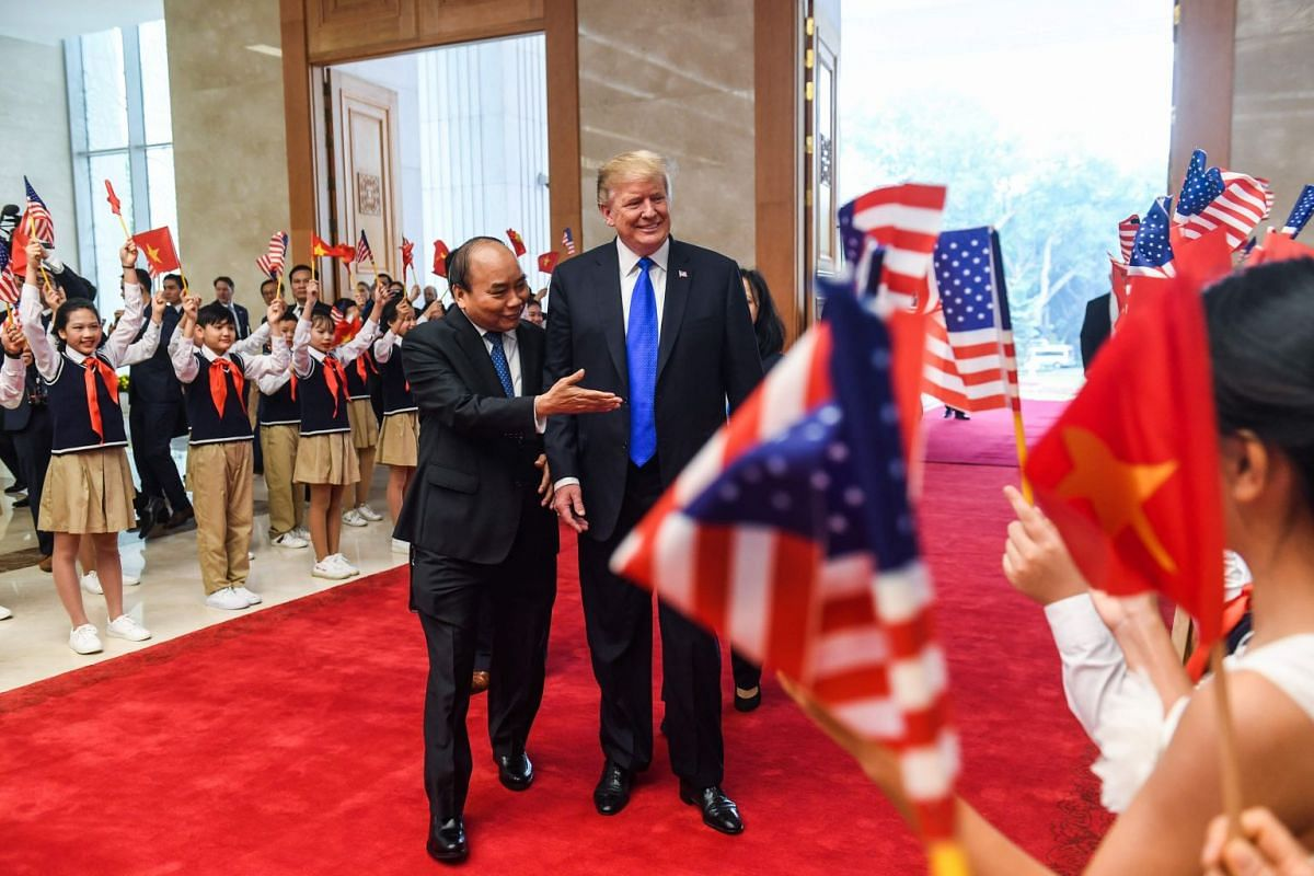 Vietnam's Prime Minister Nguyen Xuan Phuc (left) escorts US President Donald Trump upon his arrival for a meeting at the Office of Government Hall in Hanoi, on Feb 27, 2019.