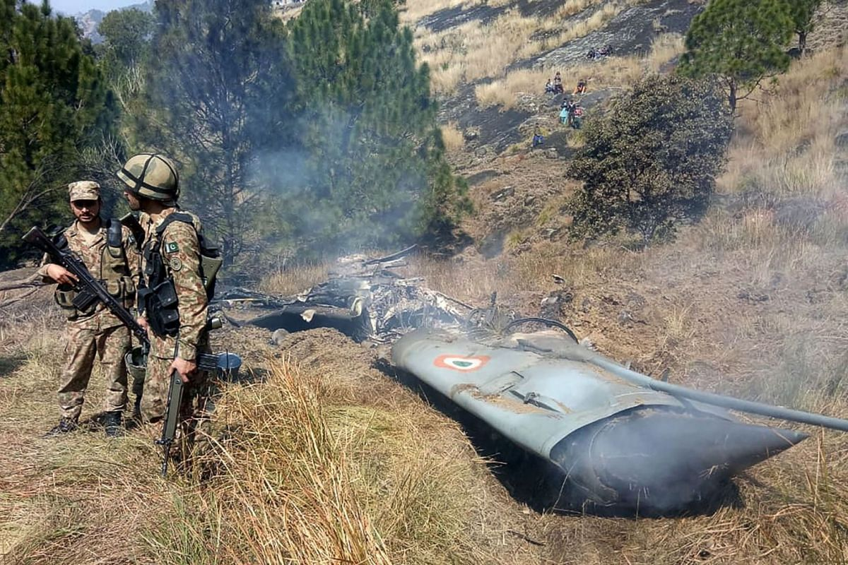 Pakistani soldiers stand next to what Pakistan says is the wreckage of an Indian fighter jet shot down in Pakistan controled Kashmir at Somani area in Bhimbar district near the Line of Control on February 27, 2019. PHOTO: AFP