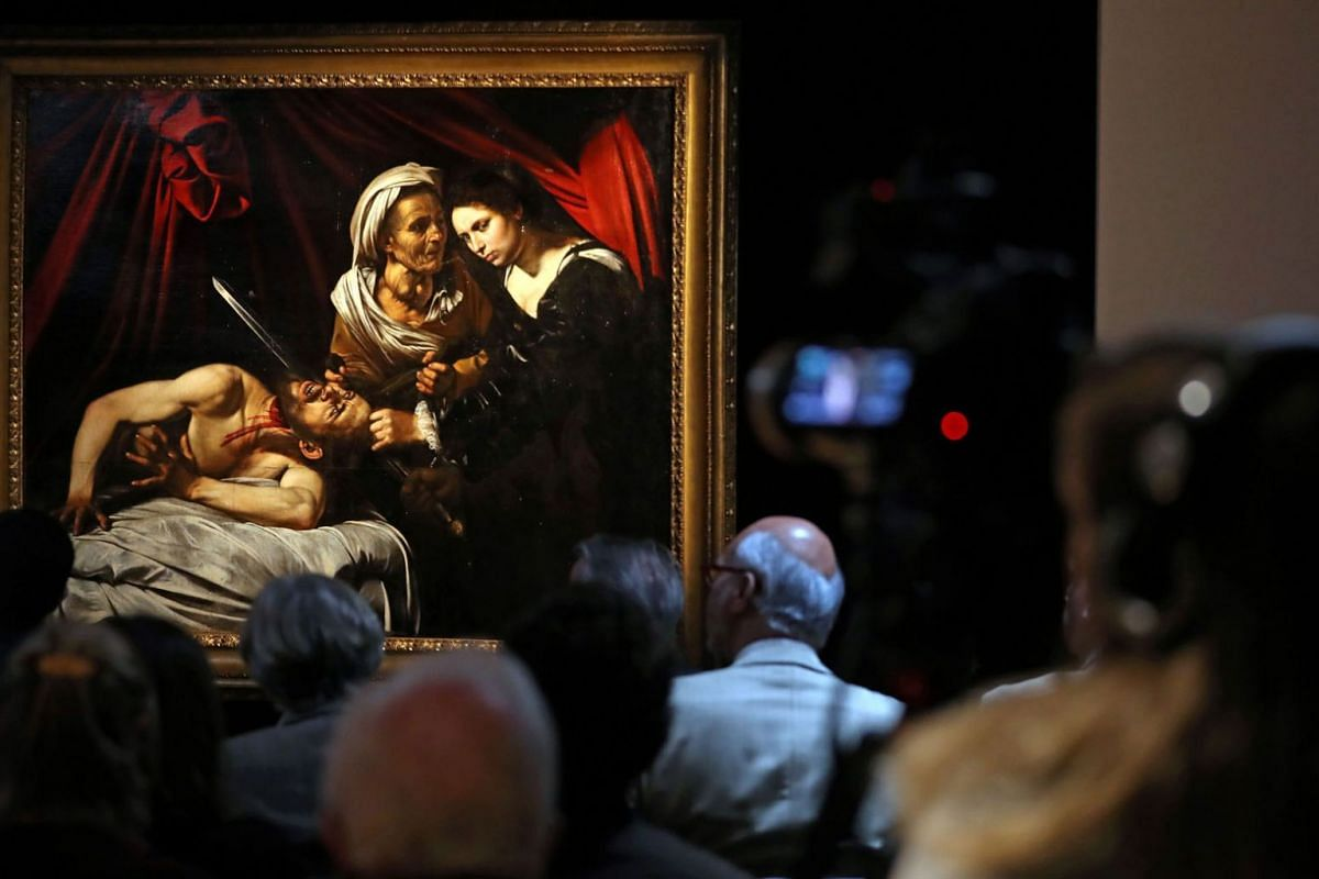 """A painting, believed to be the second version of """"Judith Beheading Holofernes"""" by Italian artist Michelangelo Merisi da Caravaggio, is picutred during a photocall in London on February 28, 2019, following its restoration. PHOTO: AFP"""