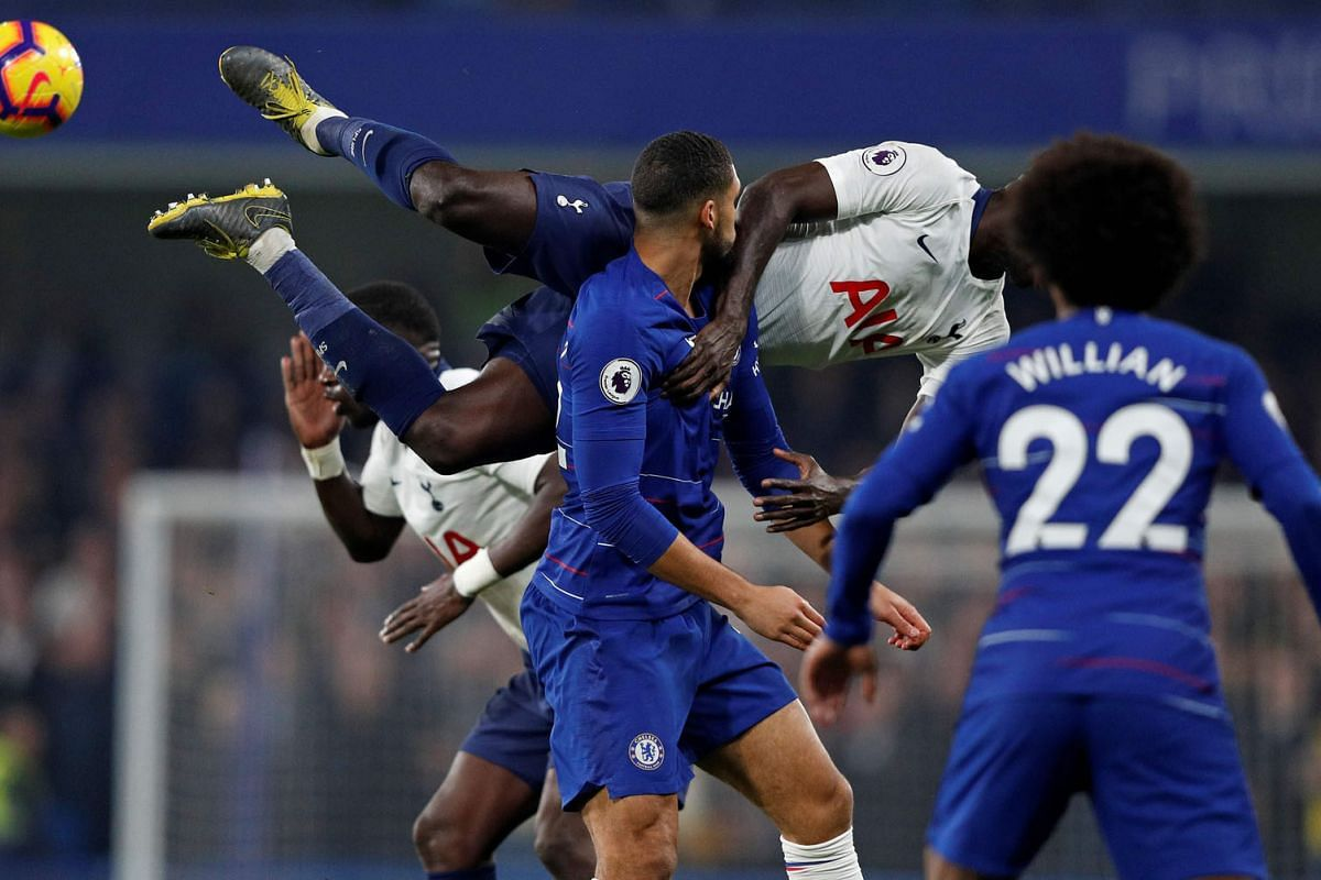 Tottenham Hotspur's Colombian defender Davinson Sanchez (C) dives as he vies with Chelsea's English midfielder Ruben Loftus-Cheek (centre L) and Chelsea's Brazilian midfielder Willian (R) during the English Premier League football match between Chels