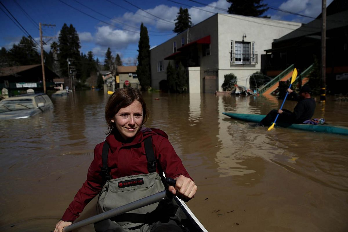 A resident paddles through a flooded neighbourhood on Feb 28, 2019, in Guerneville, California.