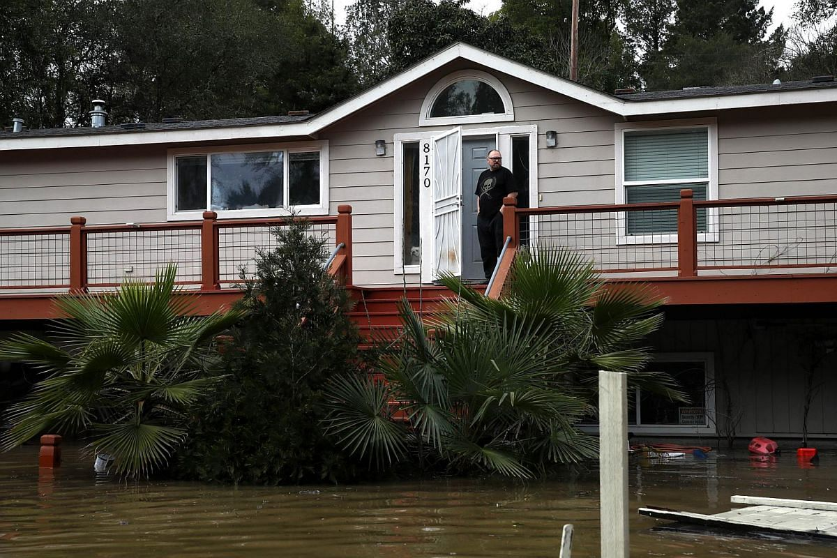 A resident stands on his porch in a flooded neighbourhood on Feb 27, 2019, in Forestville, California.