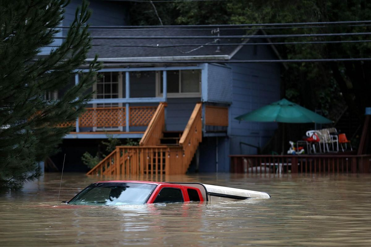 A car sits underwater in a flooded neighbourhood on Feb 27, 2019, in Forestville, California.