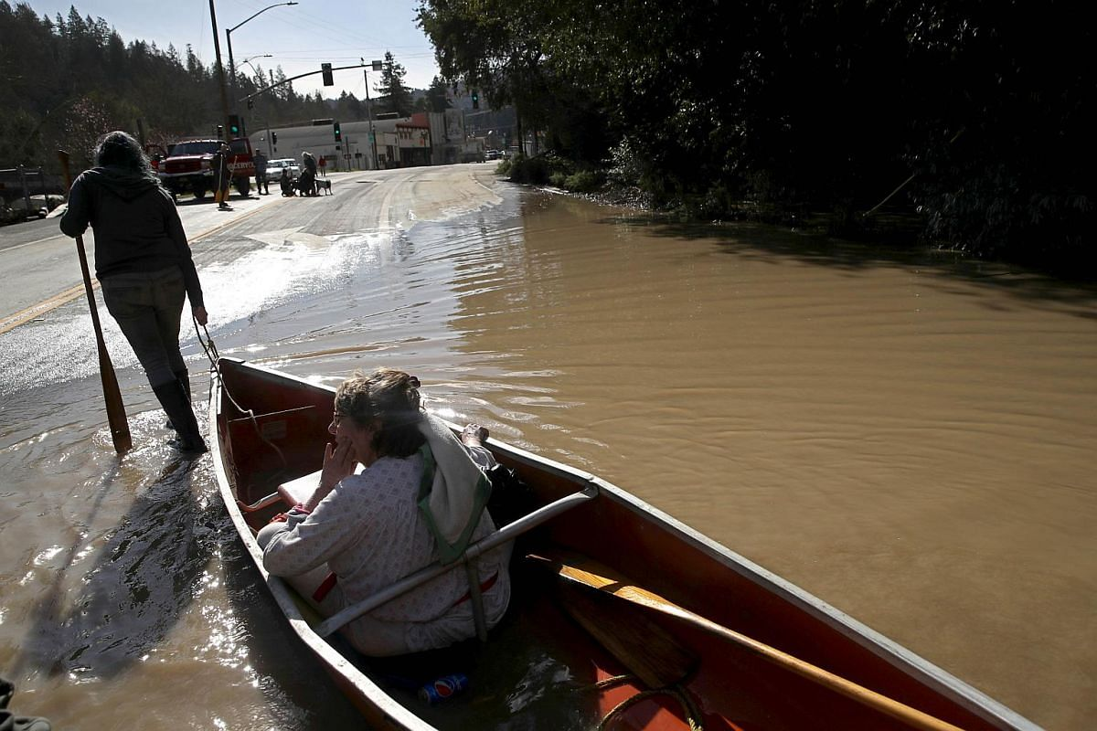 A resident is pulled to dry land in a canoe near a flooded neighbourhood on Feb 28, 2019, in Guerneville, California.