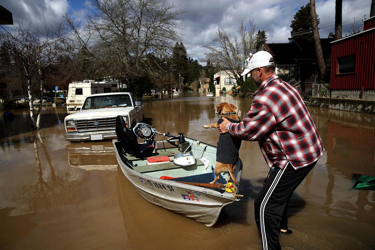 A resident puts his dog in his boat before navigating through a flooded neighbourhood on Feb 28, 2019, in Guerneville, California.