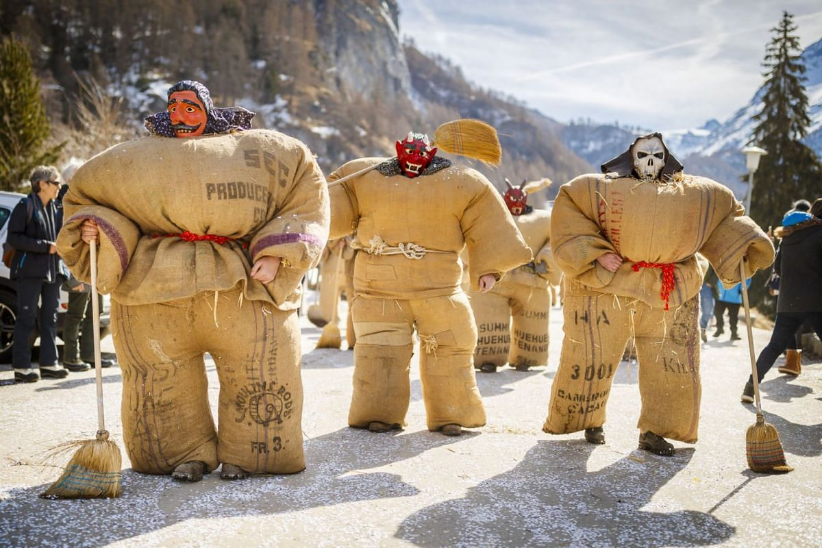 Men dressed with traditional 'Straw man' costumes and devil or sorcerer masks join the carnival parade in the alpine village of Evolene, Switzerland, March 3, 2019. PHOTO: EPA-EFE