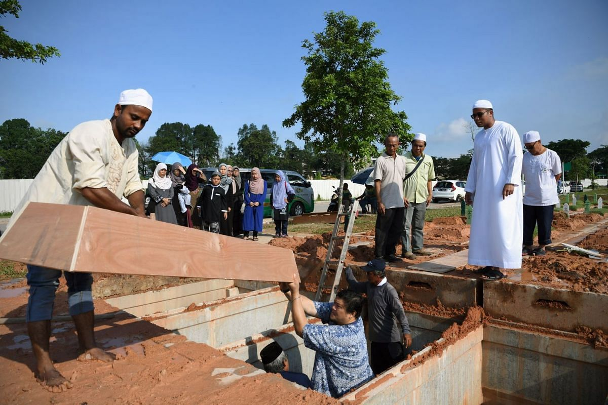 Undertaker Muhammad Razaly Osman (second from right) and participants in the Jenazah Management Course watch workers lift a wooden plank casing called papan long into a grave to be placed over the body during a burial at the Pusara Aman Cemetery in Lim Ch