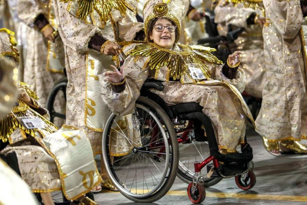 A reveller in a wheelchair, part of the Rosas de Ouro samba school, performs at the Carnival at the Sambodrome in Sao Paulo, Brazil, on March 3, 2019.