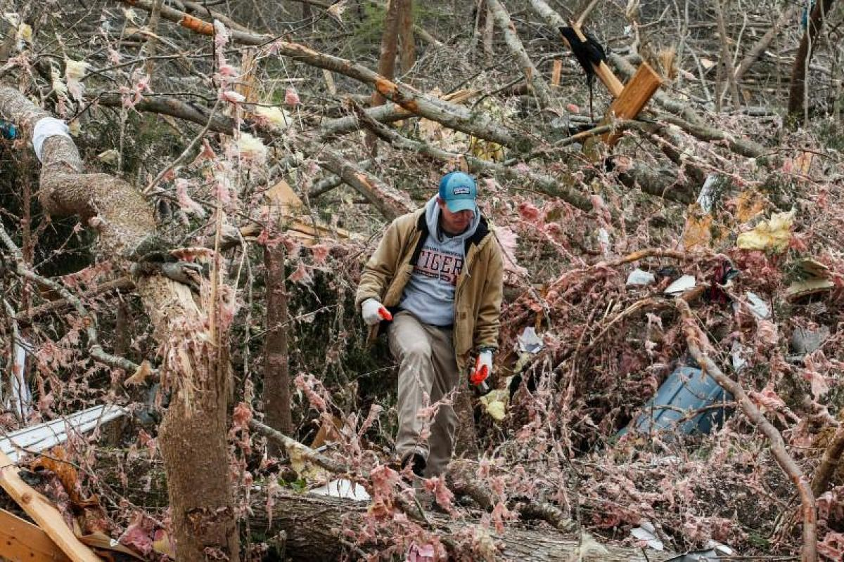 Mr Joey Roush walks through debris on March 4, 2019, at his mother's home after it was destroyed in a tornado in Beauregard, Alabama.