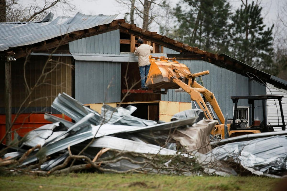A man works on a damaged building the morning after two back-to-back tornadoes touched down in Beauregard, Alabama, on March 4, 2019.