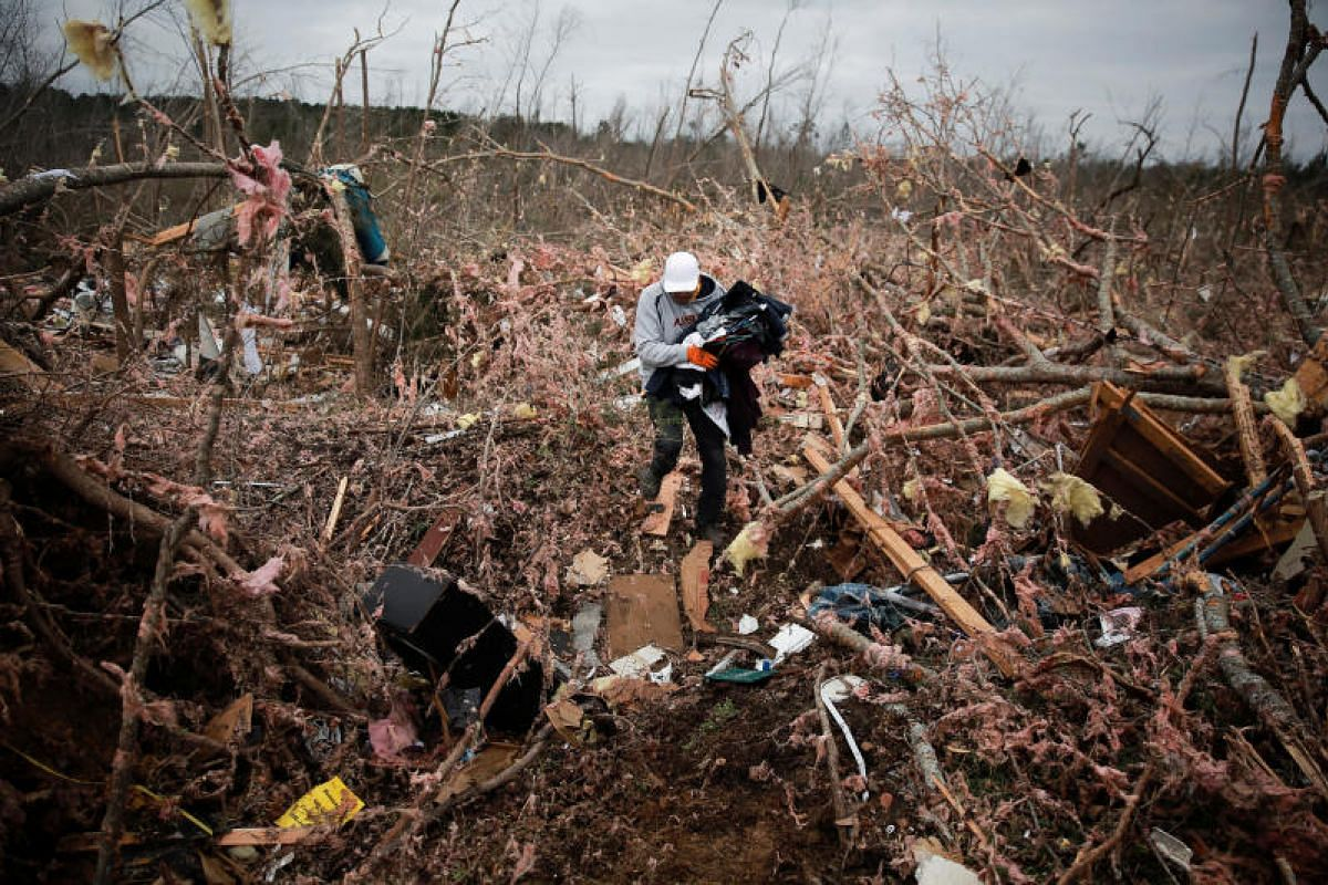 Mr Dax Leandro salvages clothing from the wreckage of his friend's home after two back-to-back tornadoes touched down in Beauregard, Alabama, on March 4, 2019.