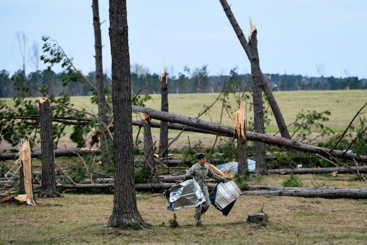 A man cleans up debris among twisted trees in an area hit by a tornado yesterday in Beauregard, Alabama, on March 4, 2019.