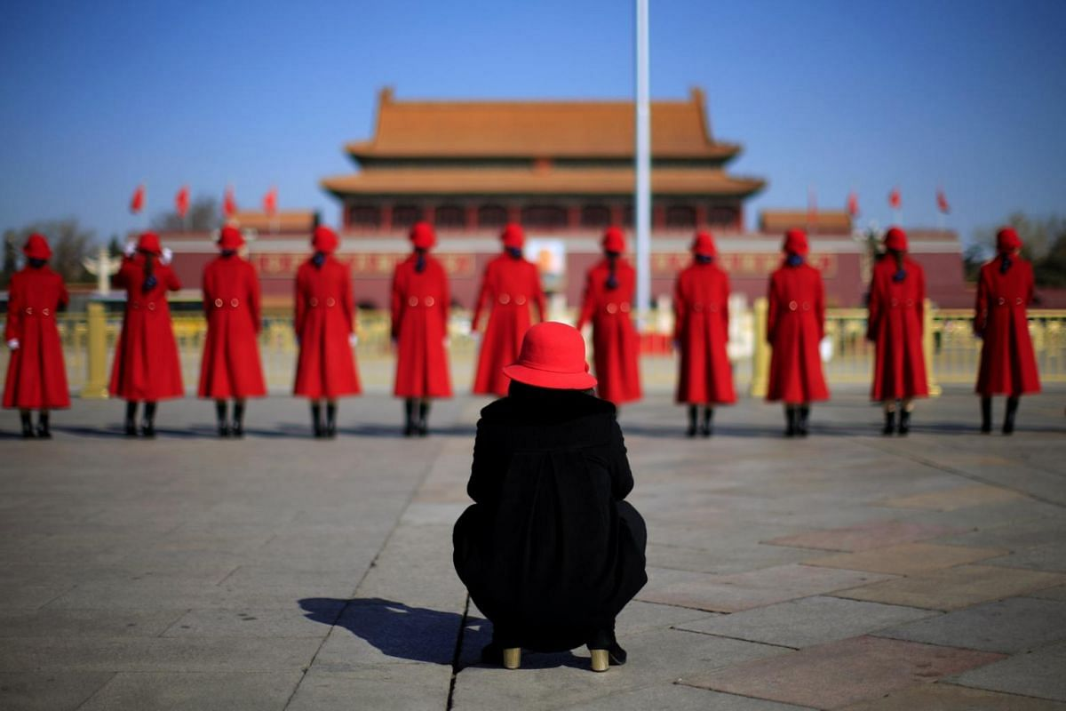 Attendants wait outside the Great Hall of the People during  opening of the second session of the 13th National People's Congress.