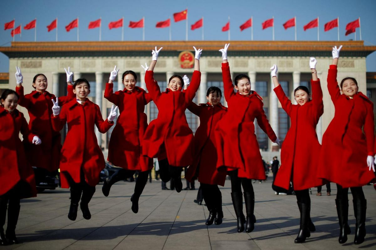 Attendants pose for a picture outside the Great Hall of the People during the opening of the second session of the 13th National People's Congress.