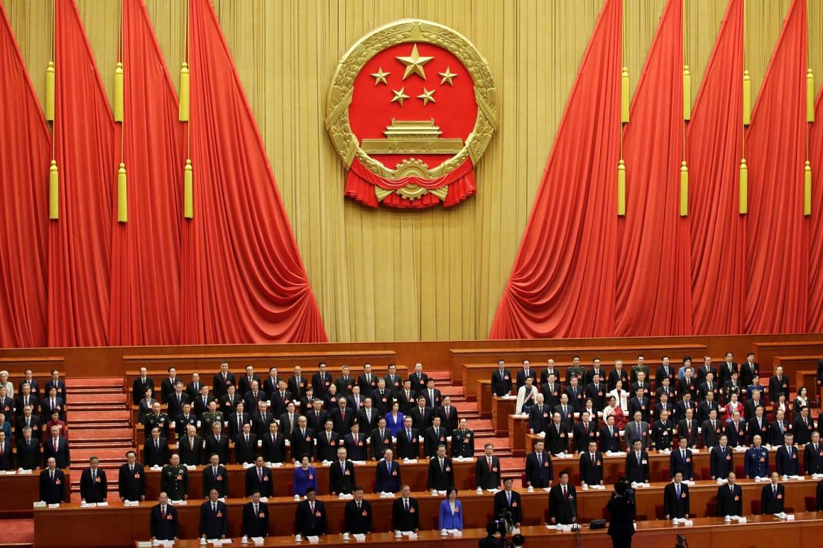 Officials sing the national anthem during  the opening of the second session of the 13th National People's Congress.