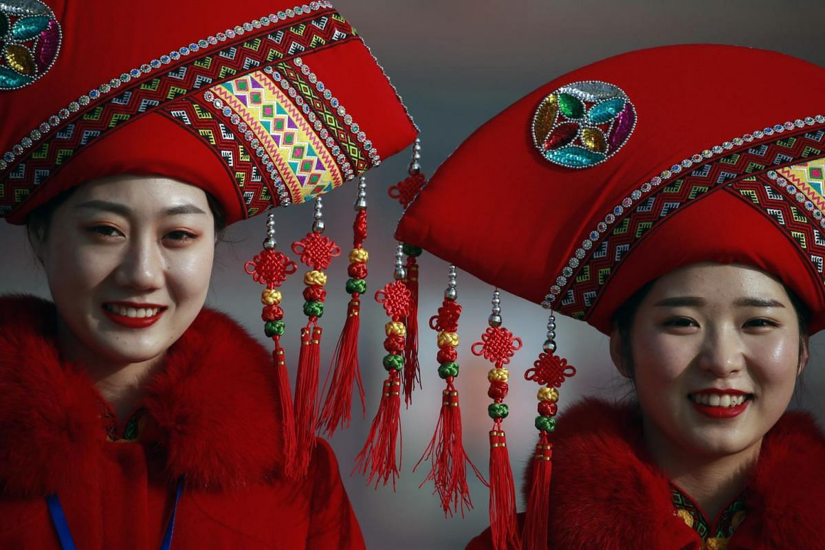 Chinese stewardesses in ethnic minority costumes pose for photos in Tiananmen Square before the opening of the second session of the 13th National People's Congress.