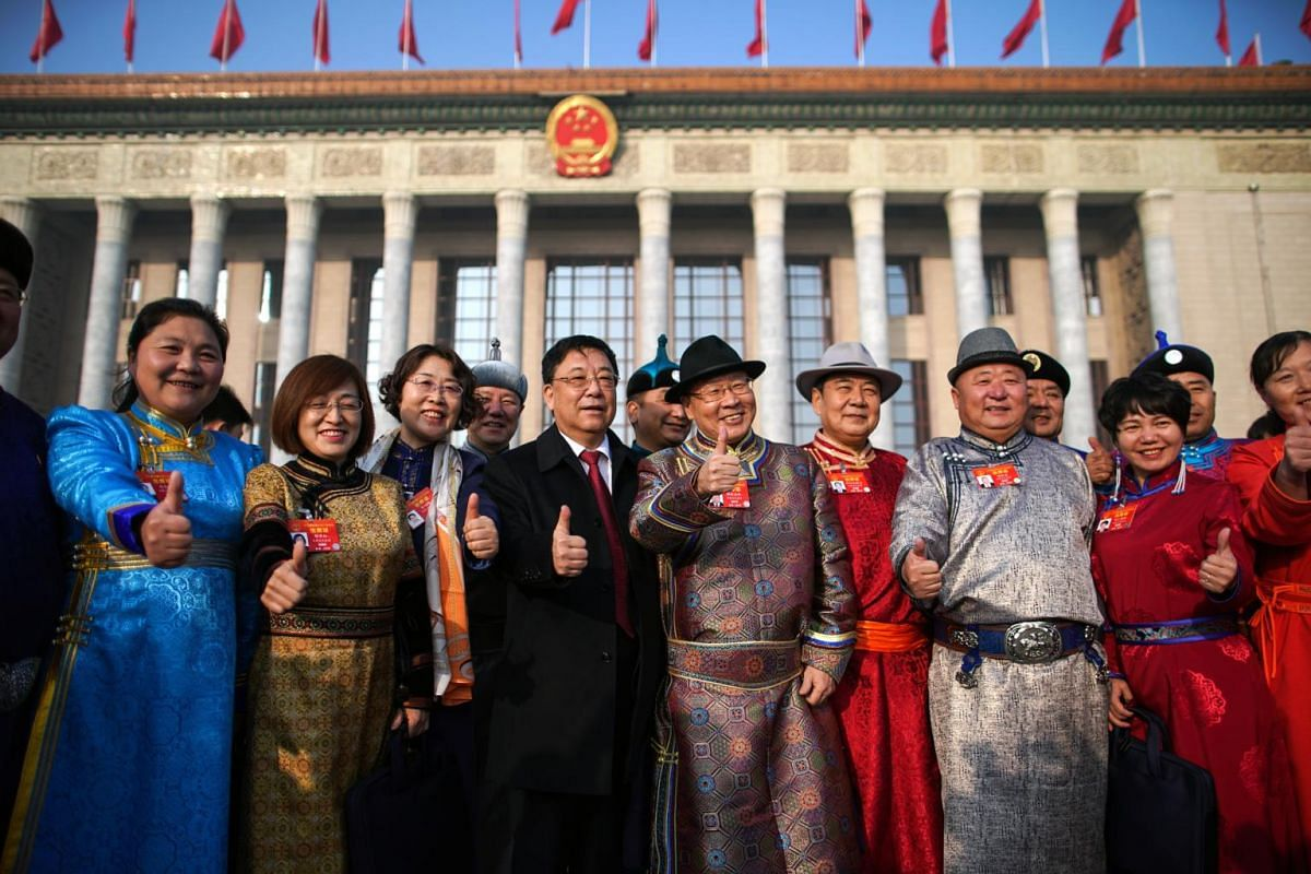 Delegates pose for a photo outside the Great Hall of the People as they arrive for the opening of the second session of the 13th National People's Congress.