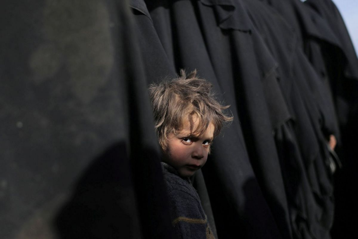 A boy looks stands in line to receive aid near Baghouz, Deir Al Zor province, Syria, on March 5, 2019. Photo: REUTERS