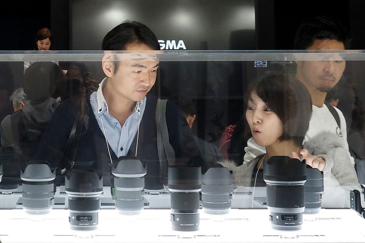 Visitors to the annual CP+ Camera & Photo Imaging Show in Yokohama, Japan, checking and trying photographic equipment on the show floor (above) .