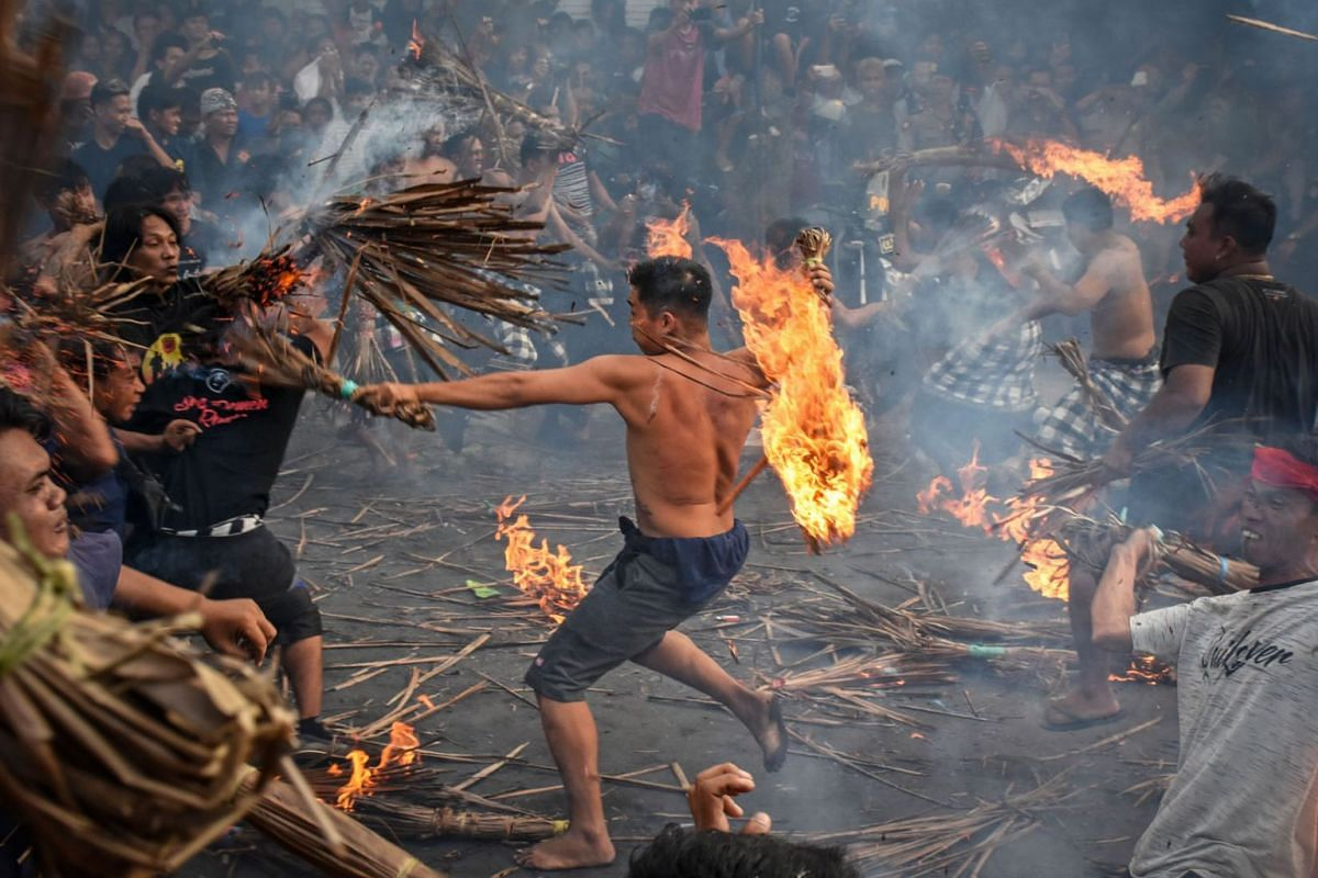 """Hindu devotees participate in a traditional activity known locally as """"Perang Api"""" or fire war one day ahead of Nyepi in Mataram, Indonesia on March 6, 2019. PHOTO:  AFP"""
