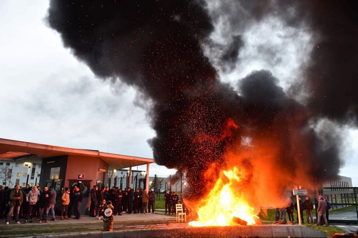 Waste burns as prison guards block the entrance to the penitentiary center of Alencon, in Conde-sur-Sarthe, north-western France, on early March 6, 2019, a day after a prison inmate seriously wounded two guards in a knife attack before being detained