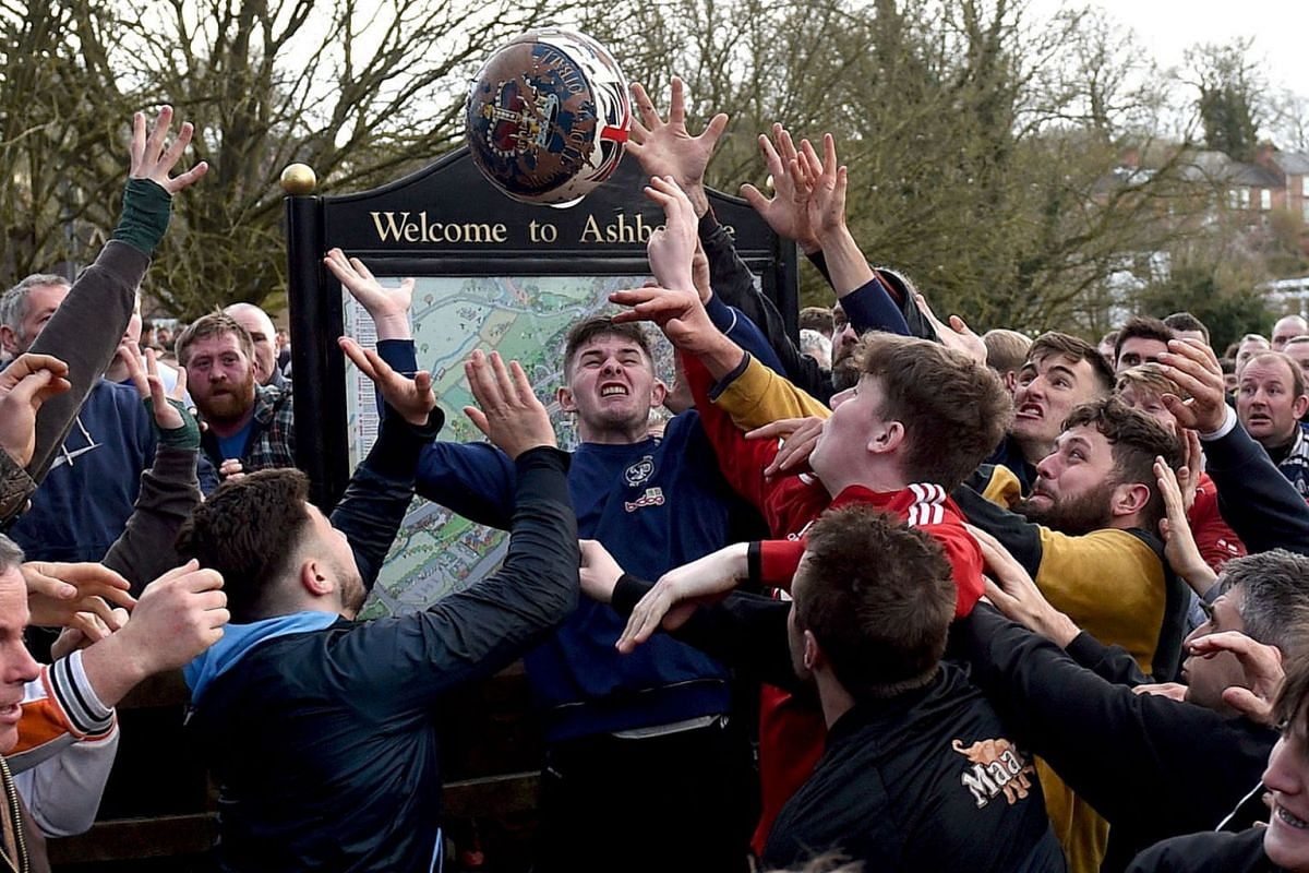 Competitors from the opposing teams, the Up'ards and the Down'ards, reach for the ball during the annual Royal Shrovetide Football Match in Ashbourne, northern England, on March 5, 2019. PHOTO: AFP